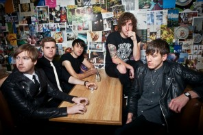 Matt Bowman, sitting on a table with bandmates